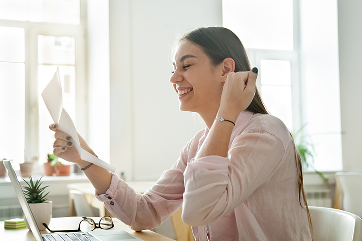 Happy female worker excited getting business letter with promotion news, satisfied woman celebrating corporate success reading report with great result or personal achievement. Rewarding concept